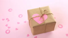 Gift box wrapped in recycled paper and decorated with pink heart. - stock footage