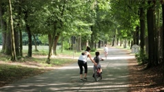 Woman teaching bicycle to her little girl Stock Footage