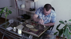 Man with a brush paints a picture varnish Stock Footage