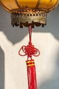 Red Chinese knot decoration attached to a traditional lantern Stock Photos
