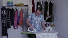 Man ironing a shirt Stock Footage