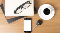 Coffee,phone,car key,eyeglasses and stack of book Stock Photos