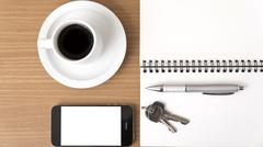 coffee cup with phone car key and notepad - stock photo