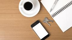 Coffee cup with phone car key and notepad Stock Photos