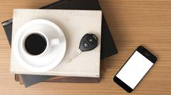 Coffee cup with phone car key and stack of book Stock Photos
