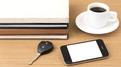 coffee cup with phone car key and stack of book - stock photo