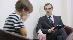 pretty male psychiatrist looking at patient during her visit - stock footage