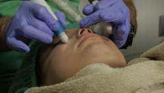 Beautician cleaning face of female customer,facial cleansing close up,beauty spa Stock Footage