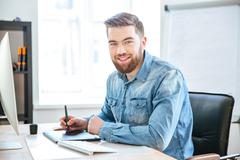 Happy designer working using pen tablet with stylus in office - stock photo