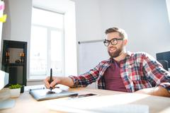 Smiling bearded designer drawing and using graphic pen tablet Stock Photos