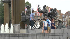 Man sitting and posing on a bicyclist statue in 't Zand, Bruges Stock Footage