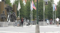 People in front of a fountain with bike statues and a woman biking and posing Stock Footage