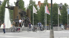 Bicyclists in front of a fountain with statues and people walking in 't Zand Stock Footage