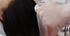 Shot of a young woman having her hair washed at a hair salon. Shot on RED Epic. Stock Footage