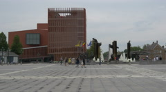 People sitting, walking and biking near the fountain in 't Zand square, Bruges Stock Footage