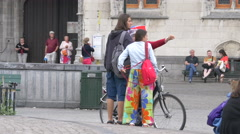 Turkish woman with umbrella hat talking to two young people in Markt, Bruges Stock Footage