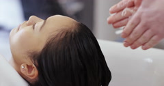 An attractive Asian woman having her hair washed at a hair salon. Stock Footage