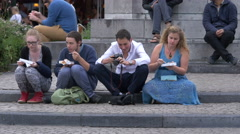 People sitting and eating and a young man looking at photos in Markt Stock Footage