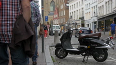 View of a parked scooter and people walking on Zuidzandstraat, Bruges Stock Footage