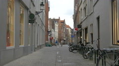 Couple walking on Dweersstraat, near parked bikes in Bruges Stock Footage