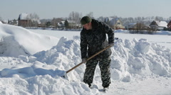 A man in camouflage clothing removes snow shovel - stock footage