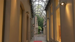 View of a narrow corridor with red carpet leading to a courtyard in Bruges Arkistovideo