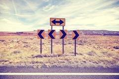Vintage stylized photo of road signs, choice concept. Stock Photos