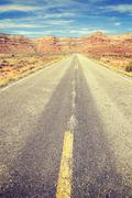 Vintage stylized country road, travel concept. Stock Photos