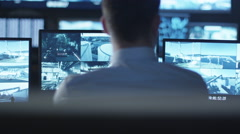 Security officer is working on a computer in a dark monitoring room Stock Footage