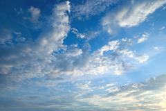 The white cumulus clouds against the blue sky - stock photo