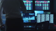 Stockbroker in white shirt is working in a dark monitoring room with displays Stock Footage