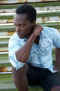 Handsome black male model sitting outdoors - stock photo