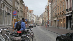 Man taking his parked bike and cars riding on Steensrtaat, Bruges Stock Footage