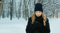 Attractive woman walking in a winter park, enjoys a smartphone Stock Footage