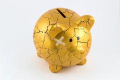 Concept of broken gold piggy bank - stock photo
