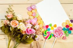 Roses flowers and empty tag for your text with heart-shaped candy on wooden b - stock photo