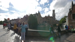 View of people standing near Dijver Canal and a boat sailing in Bruges Stock Footage