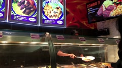 Woman ordering Chinese food at food court area Stock Footage