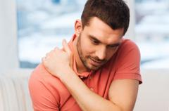 Unhappy man suffering from neck pain at home Kuvituskuvat