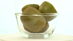 Fresh, ripe, green kiwis in rotating bowl, slow Stock Footage