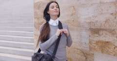 Grinning woman in sweater near wall looking over Stock Footage