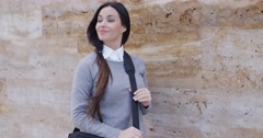 Grinning woman in sweater near wall looking over - stock footage