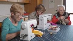 old mother with her two daughters in the kitchen sewing and talking, family, pro - stock footage