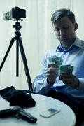 Contract killer counting his salary - stock photo