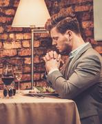 Stylish wealthy man pray before meal at restaurant. - stock photo