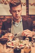 Stylish wealthy man eating at restaurant. - stock photo