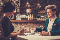 Stylish wealthy couple having desert and coffee together in a restaurant. Stock Photos