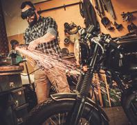 Stock Photo of Mechanic doing lathe works in motorcycle customs garage