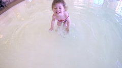 Toddler girl enjoying swimming at indoor pool. Stock Footage