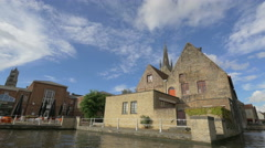 Boat sailing on Dijver Canal nearby a beautiful old building in Bruges - stock footage